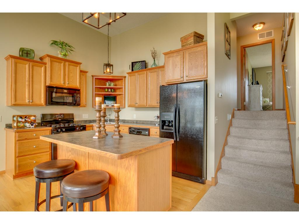 Kitchen features Oak cabinetry with flat paneled doors, staggered uppers, roll-out trash/ recycling, under cabinet lighting & a center island that seats 2-3.