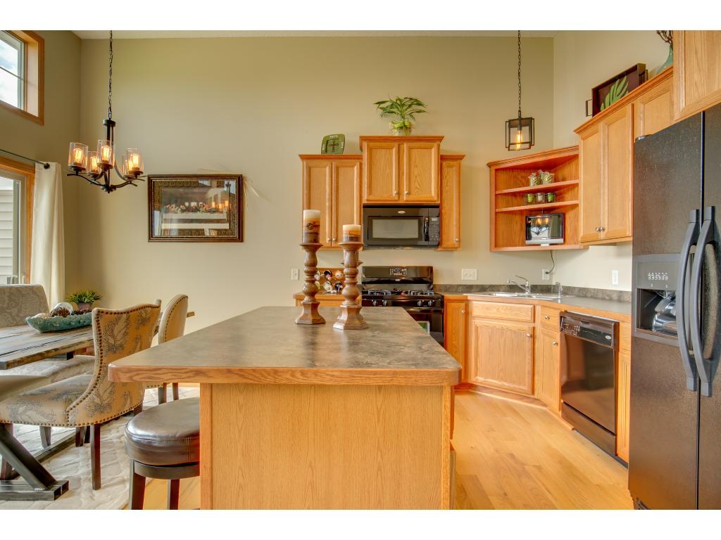 Modern light fixtures, 1 1/2 story ceilings and oak hardwood flooring.