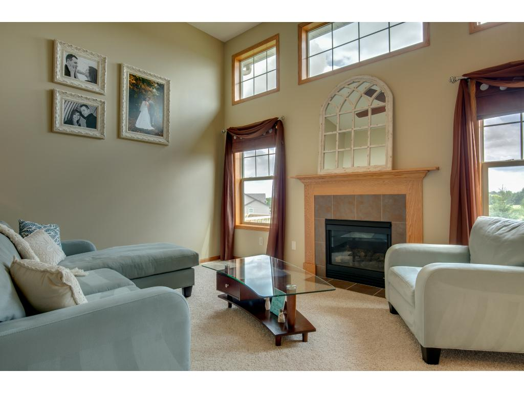 1 1/2 story living room floor to ceiling windows and gas fireplace with tile surround and oak mantle.