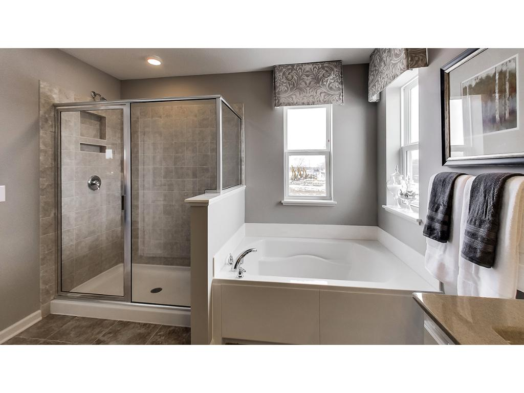 Owner bath includes separate soaking tub and huge shower.  Photos are of model.