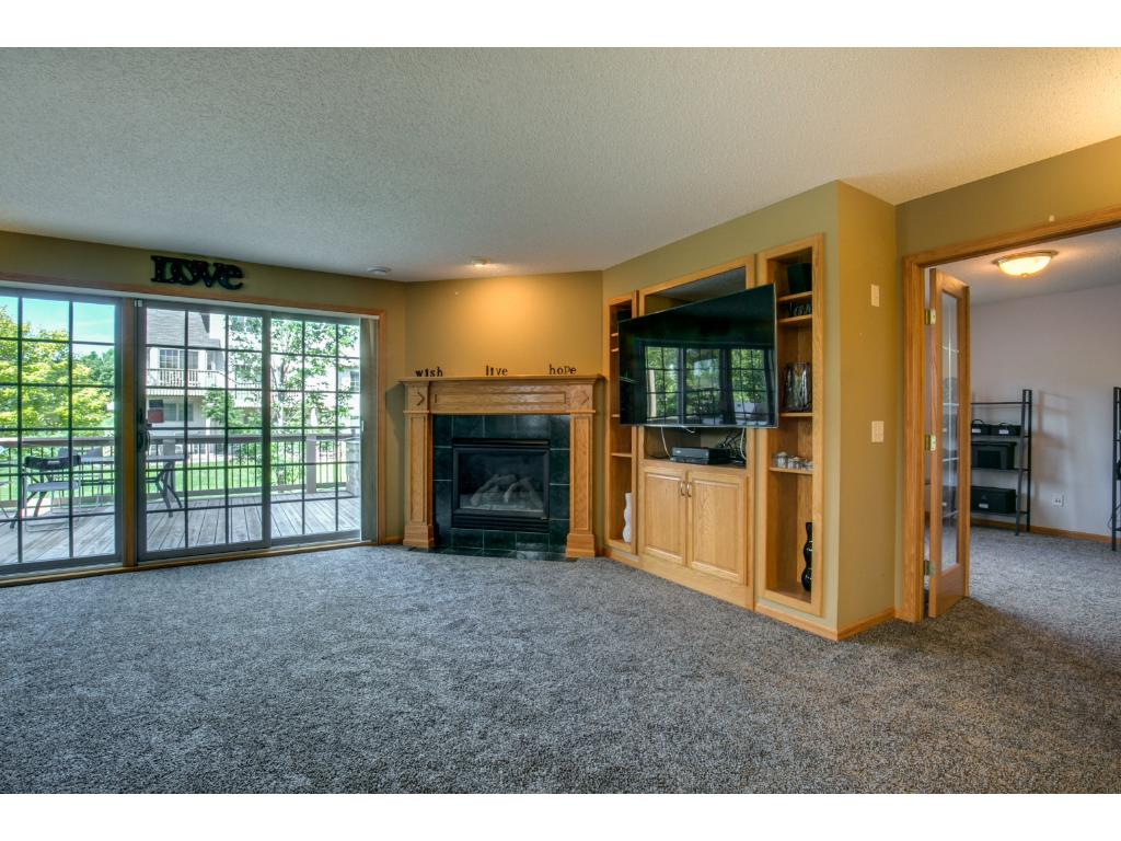 Main level Living Room with fire place, built-ins for an entertainment system.  Speakers are built-in to the walls.  A large wall of windows with sliding glass door open up to the deck allowing for lots of natural light.