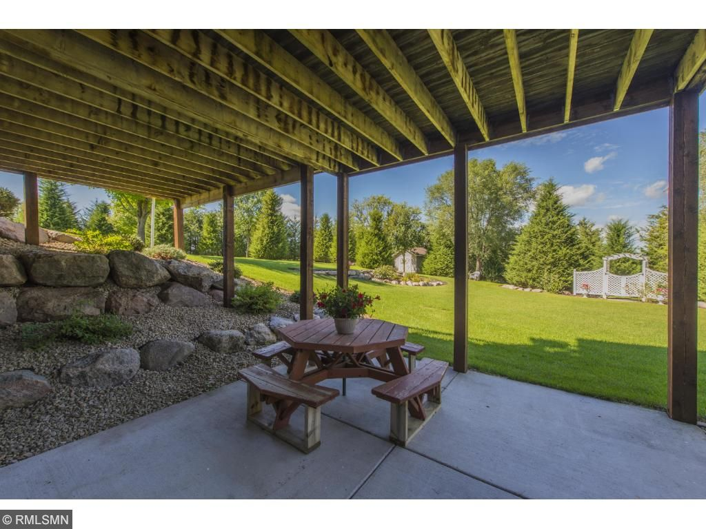 Walk out leads to a covered patio overlooking a beautiful landscaped green space, private trails for nature walks with the kids, and mature trees with tons of privacy.