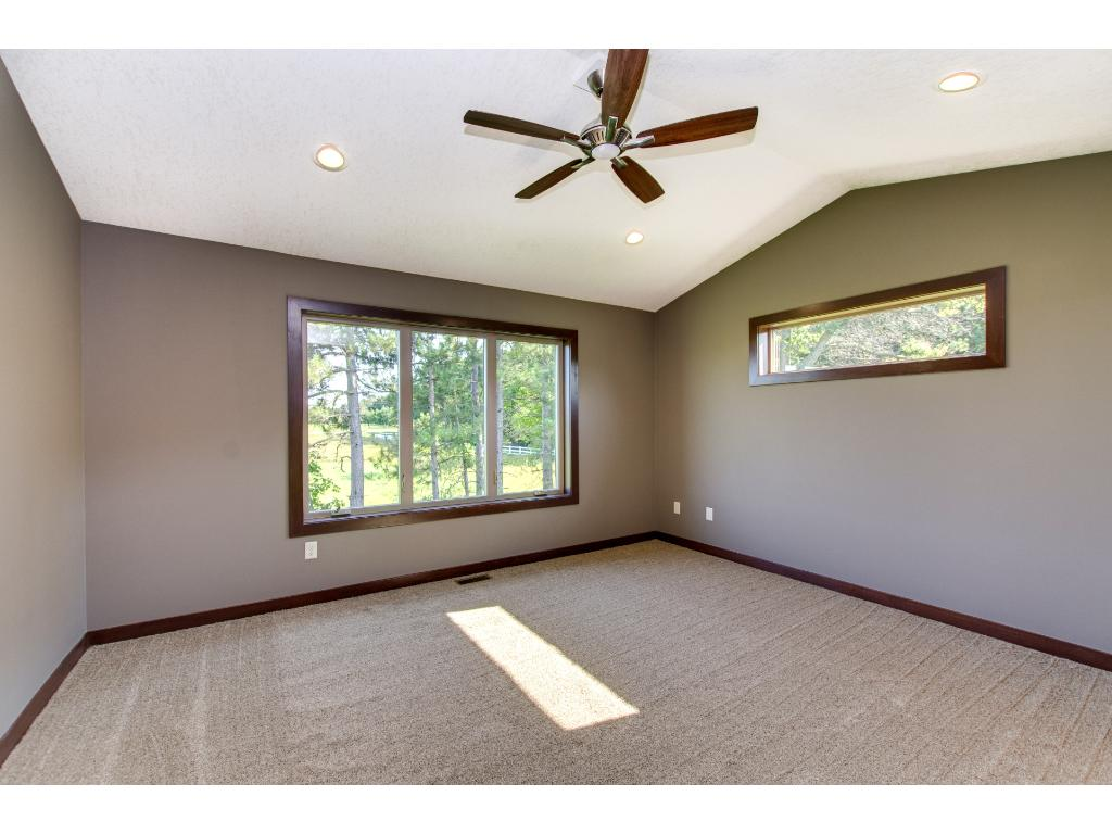 This lovely bedroom also has a vaulted ceiling, ceiling fan and plenty of light coming in.