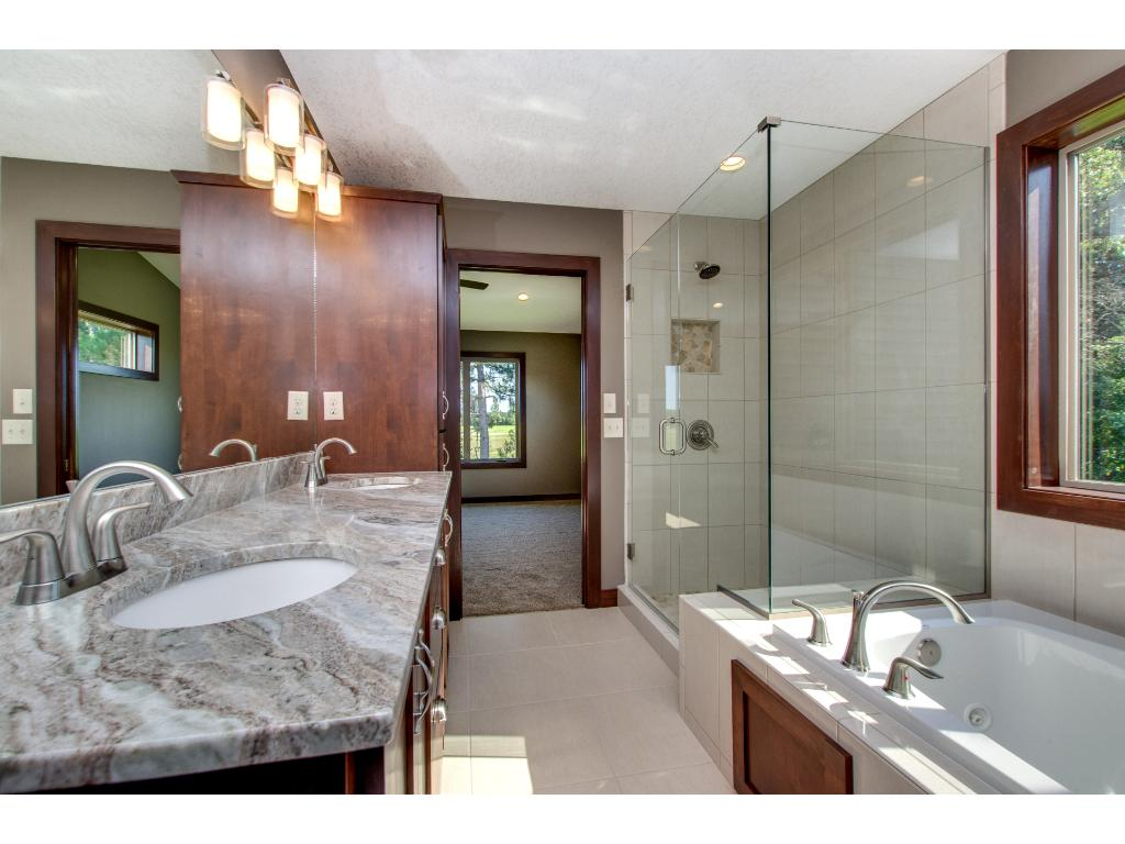 The Owner's private bath has a jetted tub and walk in Travertine stone shower.
