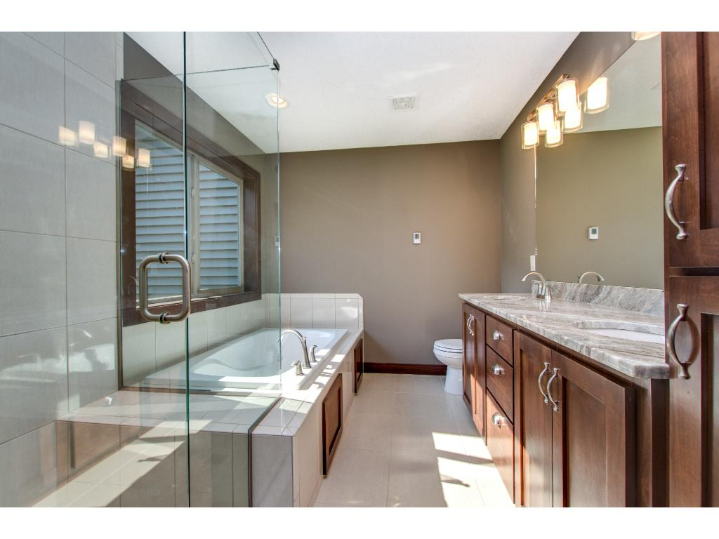 The spa like bath also has a heated tile floor, a Granite topped counter with double sinks and clear Alder cabinetry.