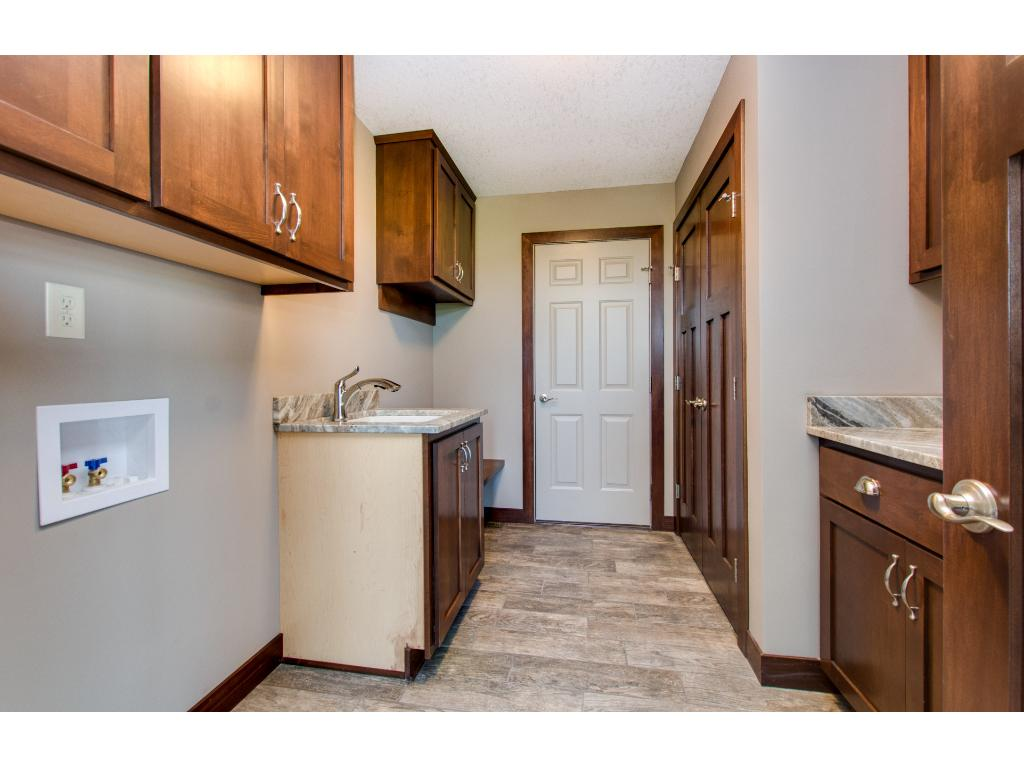 The main floor laundry has Travertine stone flooring, upper and lower clear Alder cabinetry, Granite counter top, a sink and a closet.
