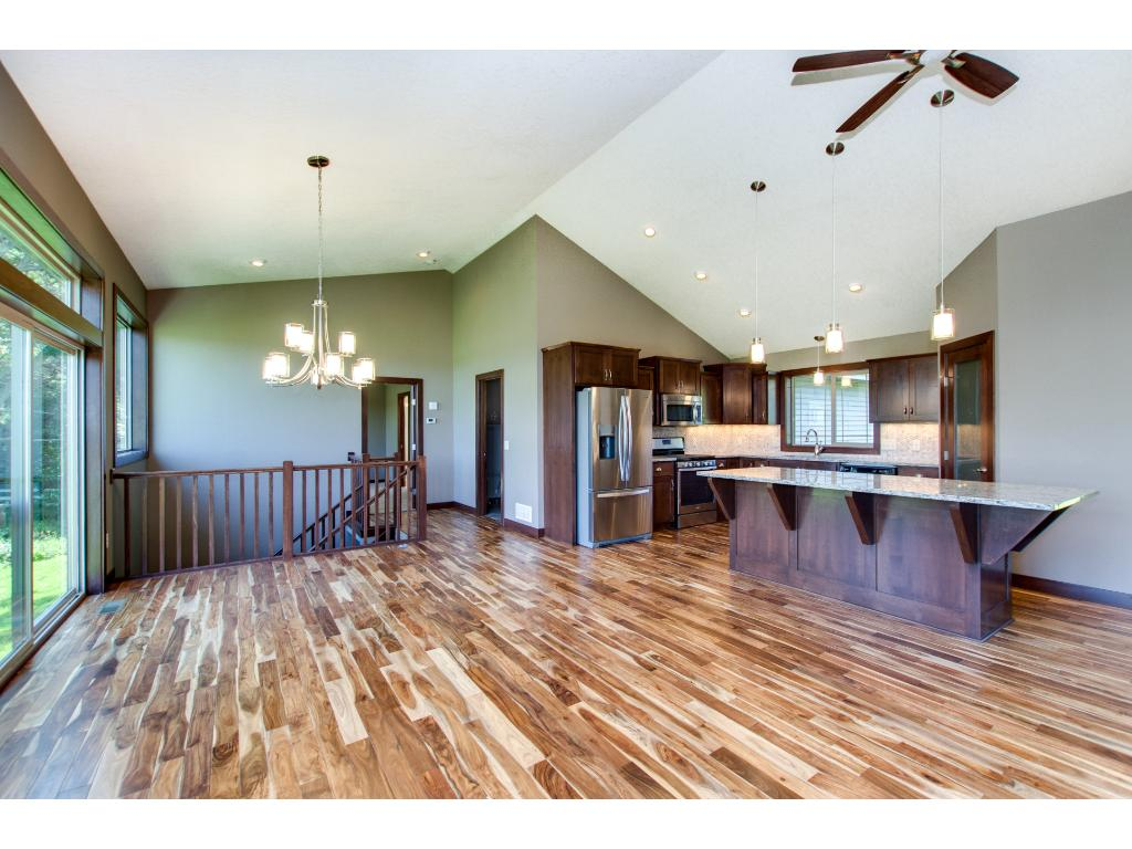 The floor plan is open with the living room, dining room and kitchen all sharing in the vibrant Acacia hardwood flooring and vaulted ceiling.