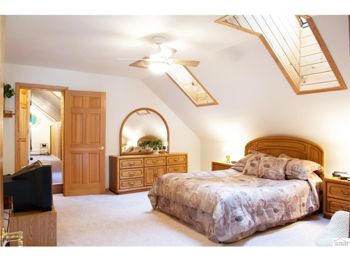 The upper level guest suite features skylights and a natural wood planked ceiling. 11683 E. Point Rd