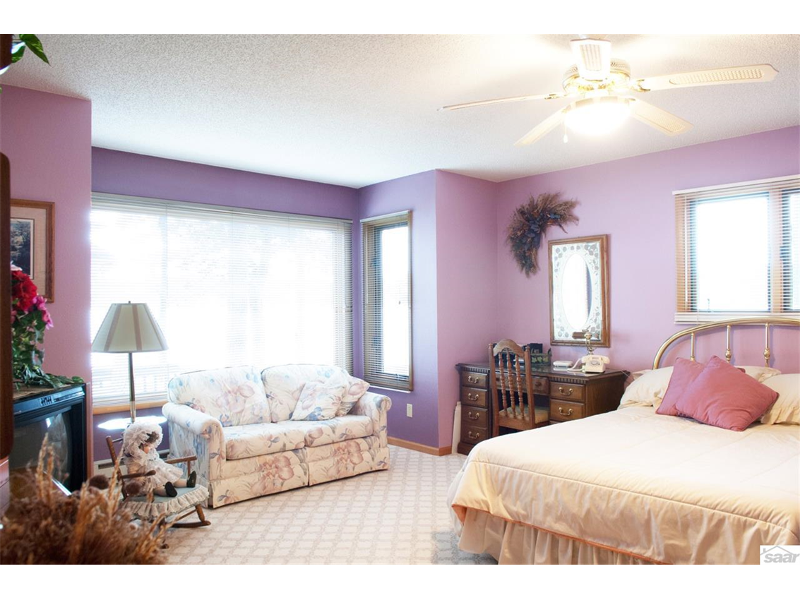 This bright main floor master suite features a large picture window with great lake views.